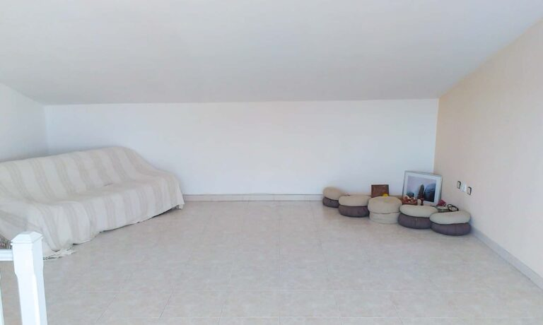 Ein Studio mit Sofa un Yoga Utensilien.