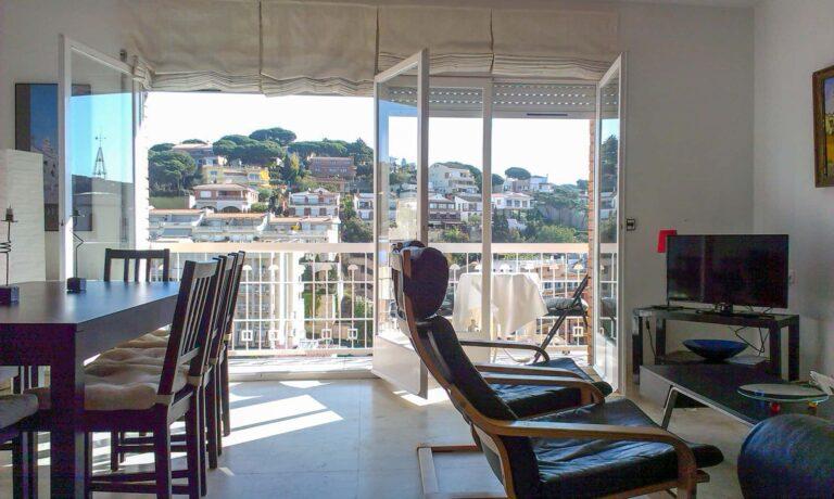 Ein Wohnzimmer bestückt mit zwei Wohnzimmerstühlen, ein Essbereich, ein TV und einen Balkon.