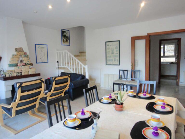 Wohnzimmerabschnitt mit Essenstisch und Küche im Hintergrund.