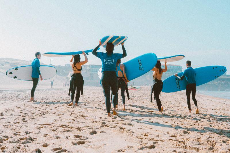 Eine Gruppe von Stand-Up Paddel Surfern gehen am Strand mit den Boards entlang.