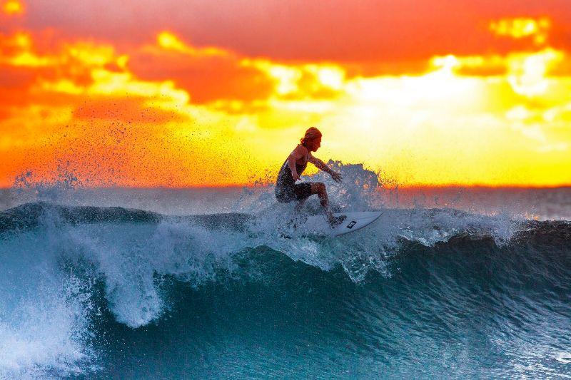 Ein Surfer reitet auf einer Welle bei Sonnenuntergang.