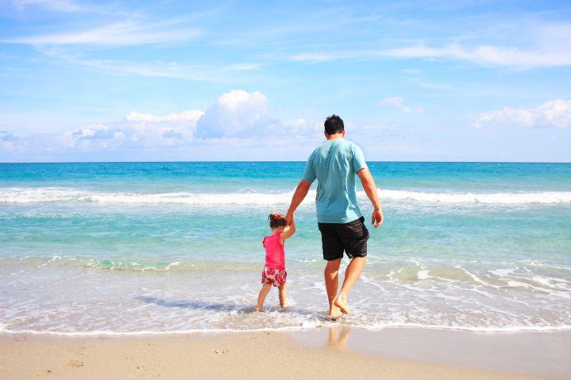 Ein Vater und seine Tochter wandern am Strand entlang.