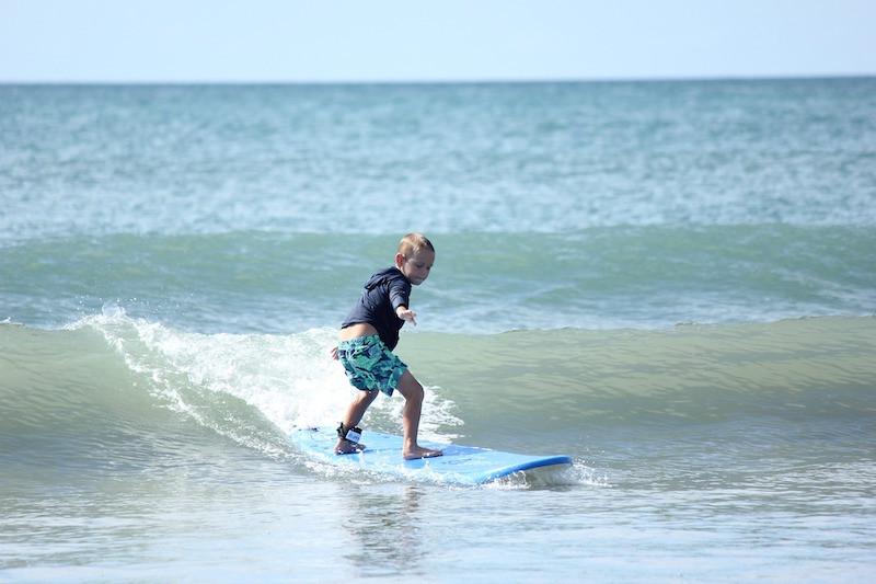 Kleiner Junge mit dem Surfboard auf einer Welle