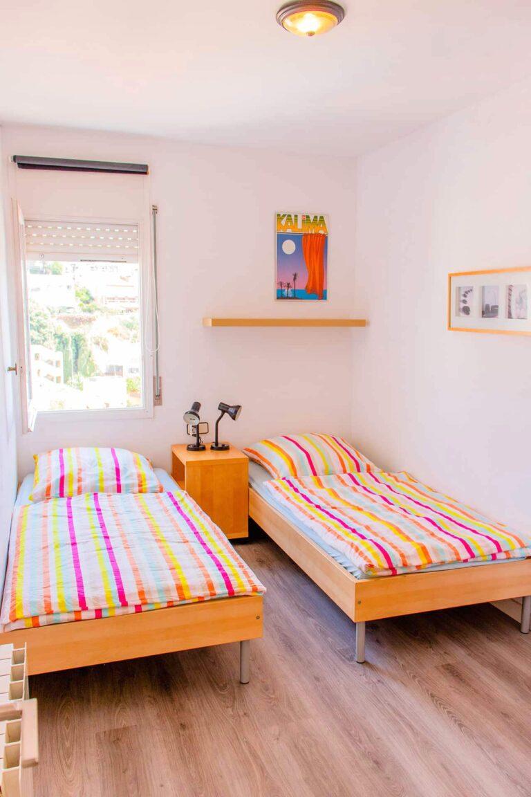Ein Schlafzimmer mit zwei bunten Einzelbetten.