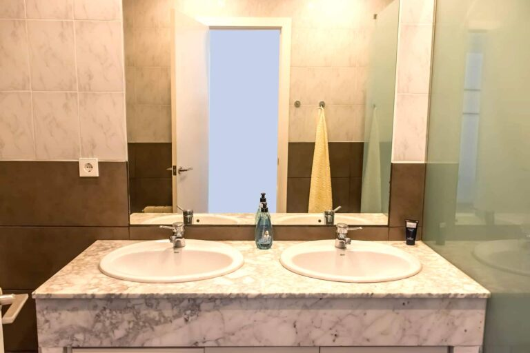 Zwei Waschbecken und ein großer Spiegel eines Marmorbads.