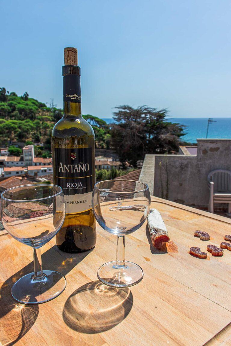 Tapas mit Wein auf einer Dachterrasse mit Meerblick.