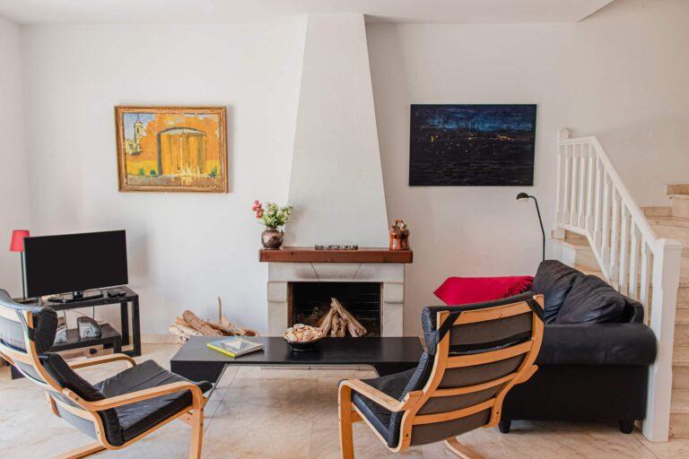 Wohnzimmerabschnitt mit Kamin und gemütlicher Sitzecke.
